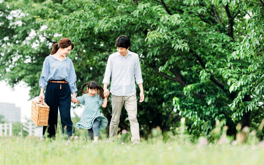 自然豊かな公園を散歩する親子